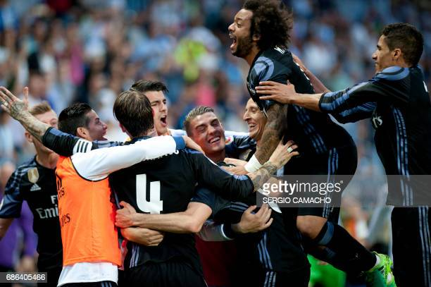 Real Madrid players celebrate a goal during the Spanish league football match Malaga CF vs Real Madrid CF at La Rosaleda stadium in Malaga on May 21...