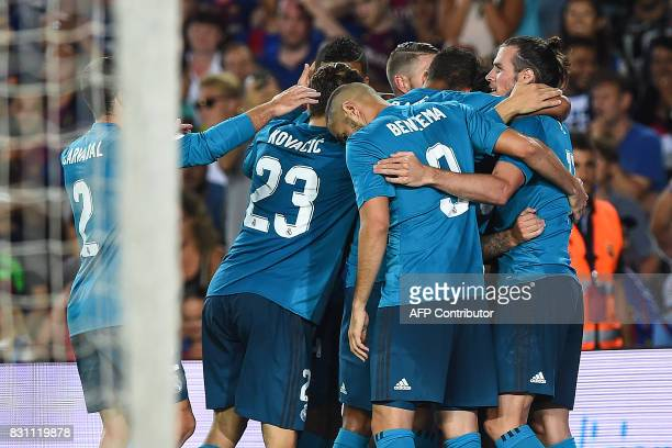 Real Madrid players celebrate Barcelona's own goal during the first leg of the Spanish Supercup football match between FC Barcelona and Real Madrid...