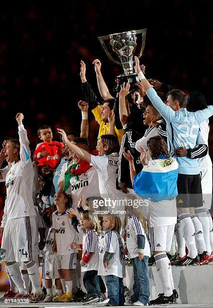 Real Madrid players celebrate holding the La Liga trophy alloft at the end of the La Liga match between Real Madrid and Levante at the Santiago...