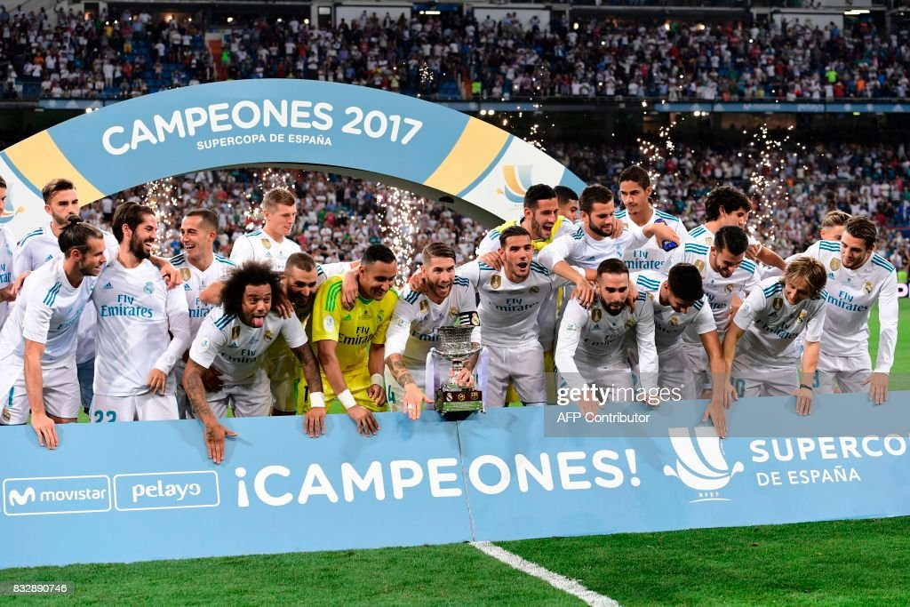 Real Madrid players celebrate their Supercup trophy after winning the second leg of the Spanish Supercup football match Real Madrid vs FC Barcelona at the Santiago Bernabeu stadium in Madrid, on August 16, 2017. /