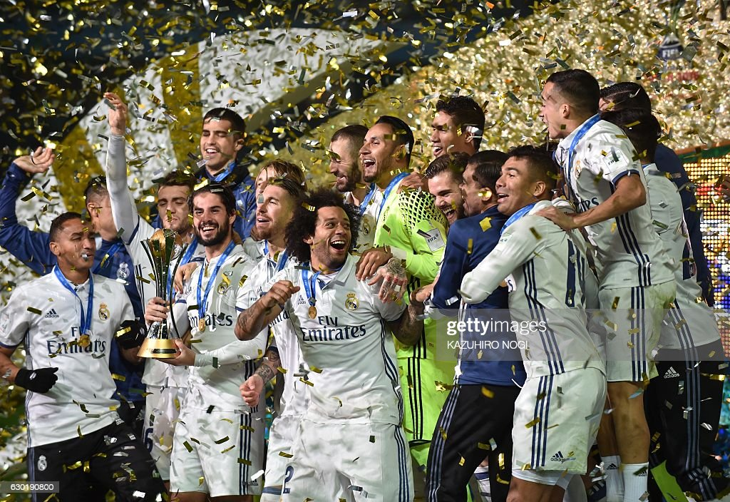 Real Madrid players celebrate with their trophy after winning the Club World Cup football final match between Kashima Antlers of Japan and Real Madrid of Spain at Yokohama International stadium in Yokohama on December 18, 2016. / AFP / KAZUHIRO