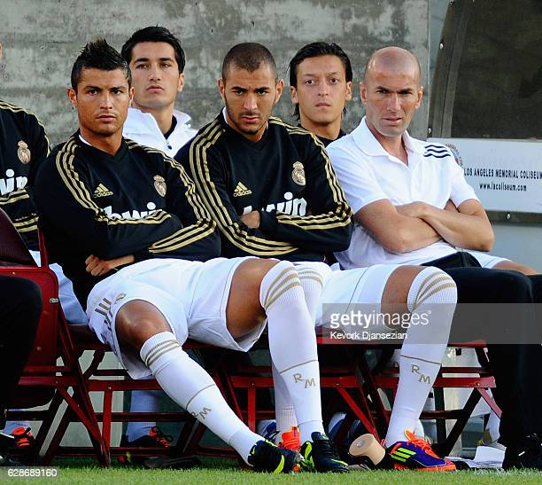 Real Madrid players Cristiano Ronaldo Karim Benzema and Zinedine Zidane Real Madrid Director of Football follow the action from bench during the...