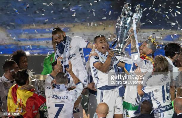 Real Madrid players hold up the trophy as they celebrate the team's win at the Santiago Bernabeu stadium in Madrid on June 4 2017 after winning the...