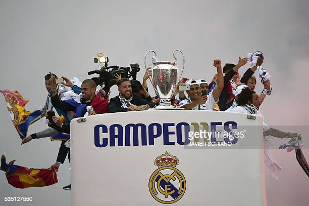 TOPSHOT Real Madrid players hold up the trophy from the bus as they celebrate the team's win arriving on Plaza Cibeles in Madrid on May 29 2016 after...