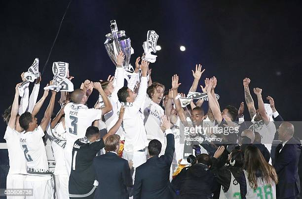 Real Madrid players raise the trophy during the celebration with their fans after winning the UEFA Champions League Final match against Club Atletico...