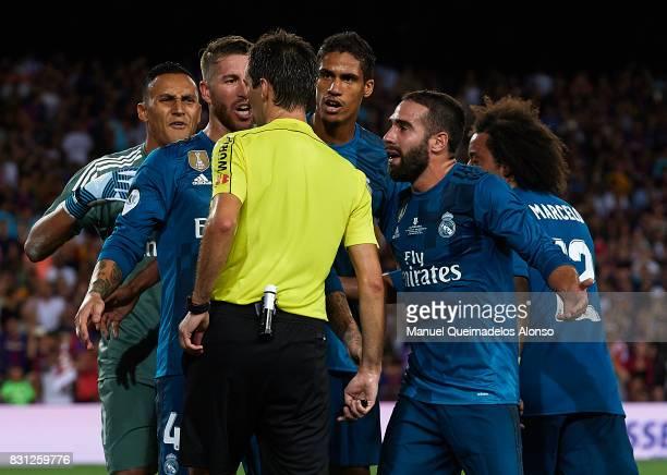 Real Madrid players surround Ricardo de Burgos Bengoetxea the referee after he awards a penalty against them during the Supercopa de Espana Supercopa...