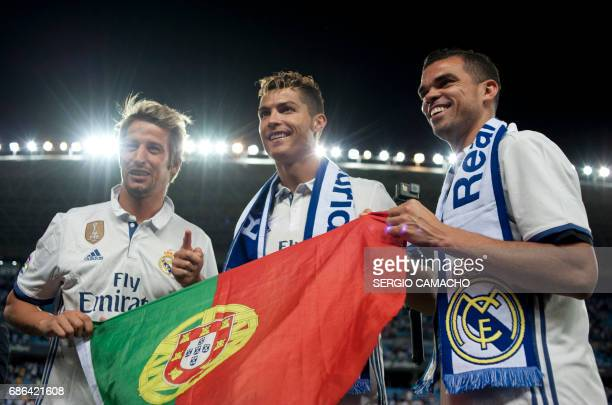 Real Madrid Portuguese players Fabio Coentrao Cristiano Ronaldo and Pepe pose with a Portuguese flag as they celebrate at the end of the Spanish...
