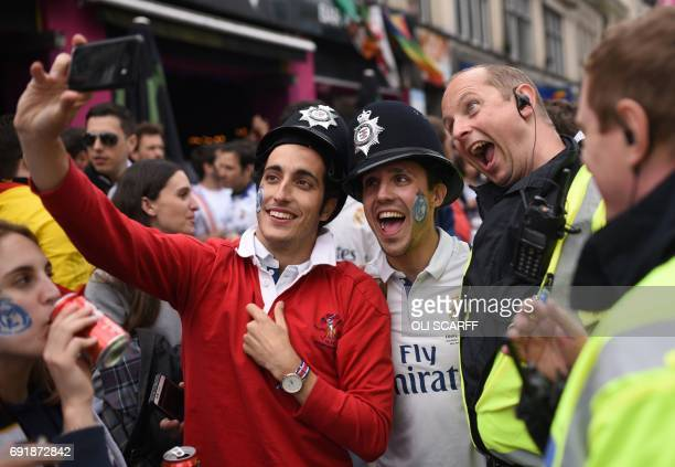Real Madrid supporters take a selfie photograph with a policeman as they enjoy the atmosphere before the UEFA Champions League final football match...