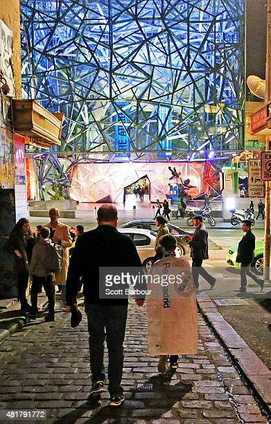 Real Madrid supporters walk down Hosier Lane past graffiti as they make their way to the MCG to attend the International Champions Cup match between...