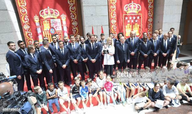 TOPSHOT Real Madrid team pose with the President of Madrid Cristina Cifuentes at the Madrid Community headquarters in Madrid on May 22 2017 during a...