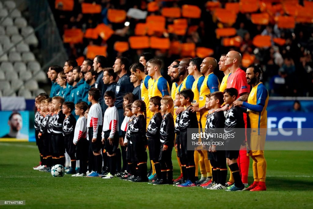Real Madrid's (background) and Apoel's (foreground) starting eleven pose for a group picture ahead of the UEFA Champions League Group H match between Apoel FC and Real Madrid on November 21, 2017, in the Cypriot capital Nicosia's GSP Stadium. / AFP PHOTO / Thomas COEX