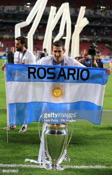 Real Madrid's Angel di Maria holds up a Argentina national flag as he celebrates with the Champions League Trophy
