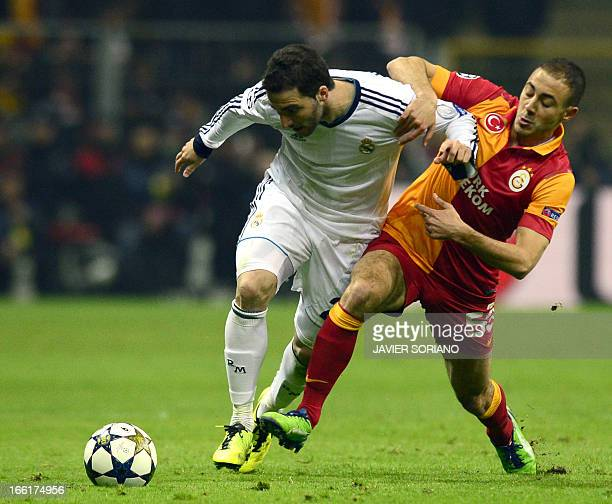 Real Madrid's Argentinian forward Gonzalo Higuain fights for the ball with Galatasaray's Moroccan midfielder Nordin Amrabat on April 9 2013 during a...