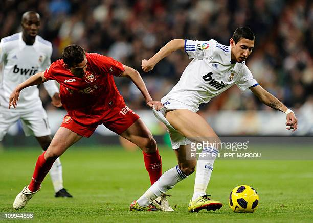 Real Madrid's Argentinian midfielder Angel di Maria vies with Sevilla's defender Fernando Navarro during the Spanish league football match Real...