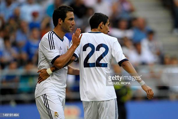 Real Madrid's Argentinian players Gonzalo Higuain congratulates Angel Di Maria on scoring against Real Oviedo during their friendly football match at...