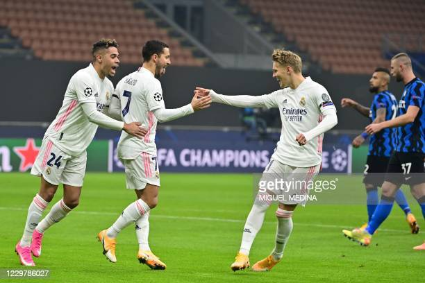 Real Madrid's Belgian forward Eden Hazard celebrates scoring a penalty with Real Madrid's Dominicans forward Mariano and Real Madrid's Norwegian...