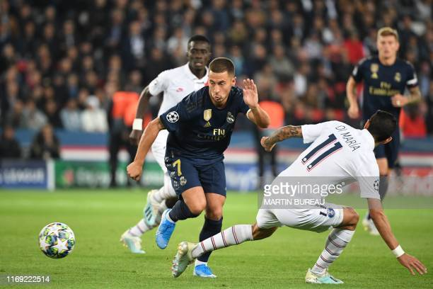 Real Madrid's Belgian forward Eden Hazard fights for the ball with Paris SaintGermain's Argentine midfielder Angel Di Maria during the UEFA Champions...