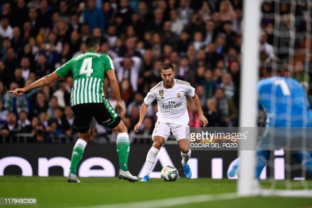 Real Madrid's Belgian forward Eden Hazard vies with Real Betis' Moroccan defender Zouhair Feddal and Real Betis' Spanish goalkeeper Joel Robles...