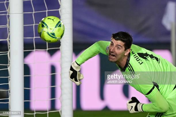 """Real Madrid's Belgian goalkeeper Thibaut Courtois eyes the ball during the """"El Clasico"""" Spanish League football match between Real Madrid CF and FC..."""