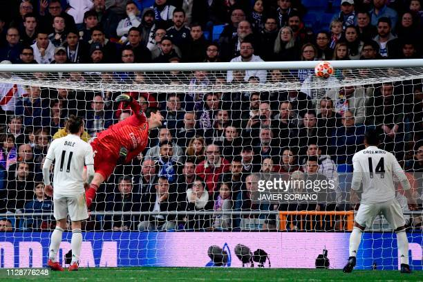Real Madrid's Belgian goalkeeper Thibaut Courtois fails to stop a ball shot by Ajax's Danish midfielder Lasse Schone during the UEFA Champions League...