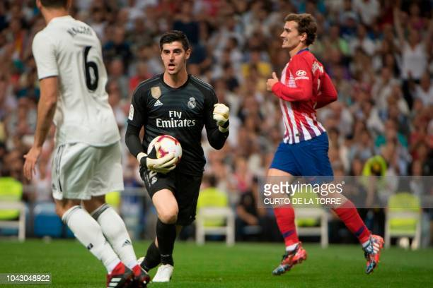 Real Madrid's Belgian goalkeeper Thibaut Courtois grabs the ball next to Atletico Madrid's French forward Antoine Griezmann during the Spanish league...