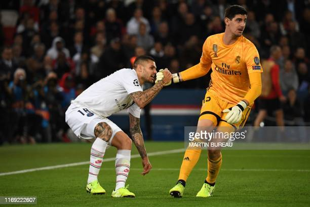 Real Madrid's Belgian goalkeeper Thibaut Courtois helps Paris SaintGermain's Argentine forward Mauro Icardi to stand up during the UEFA Champions...
