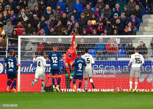 Real Madrid's Belgian goalkeeper Thibaut Courtois hits the ball with his fist during the Spanish league football match between SD Huesca and Real...