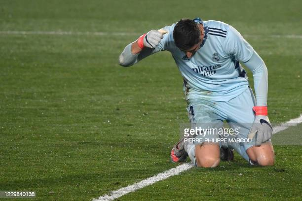 Real Madrid's Belgian goalkeeper Thibaut Courtois reacts hitting the field to Alaves' Spanish forward Joselu's goal during the Spanish League...