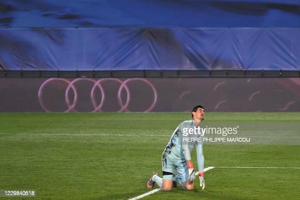 Real Madrid's Belgian goalkeeper Thibaut Courtois reacts kneeling to Alaves' Spanish forward Joselu's goal during the Spanish League football match...
