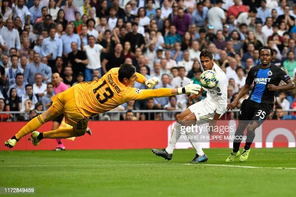 Real Madrid's Belgian goalkeeper Thibaut Courtois stop the ball next to Real Madrid's French defender Raphael Varane and Club Brugge's South African...