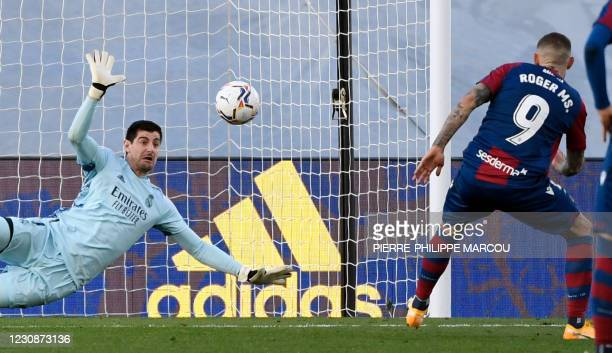 Real Madrid's Belgian goalkeeper Thibaut Courtois stops a penalty kick from Levante's Spanish forward Roger Marti during the Spanish league football...