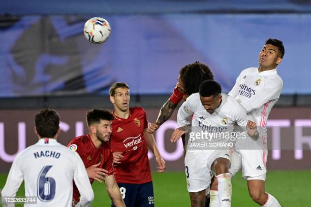 Real Madrid's Brazilian defender Eder Militao heads the ball and scores during the Spanish League football match between Real Madrid and Osasuna at...