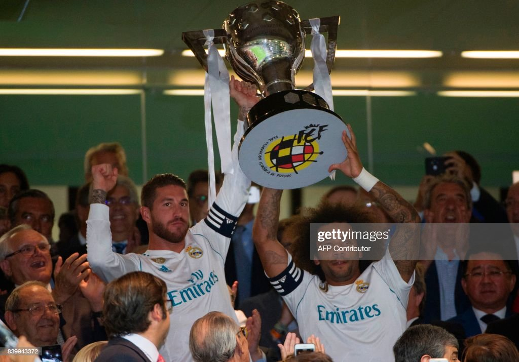Real Madrid's Brazilian defender Marcelo (R) and Real Madrid's defender Sergio Ramos hold the Spanish League cup before the Spanish league football match Real Madrid CF vs Valencia CF at the Santiago Bernabeu stadium in Madrid on August 27, 2017. /