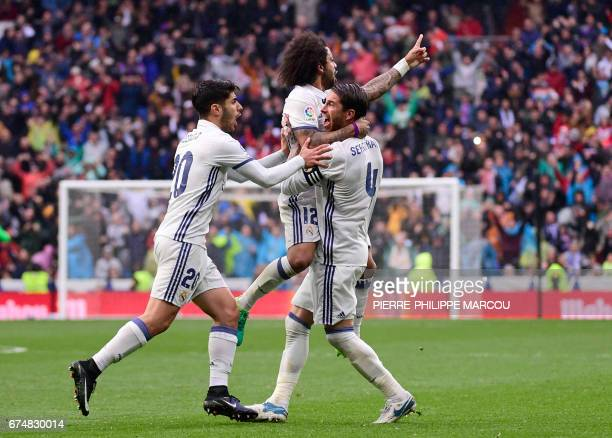 TOPSHOT Real Madrid's Brazilian defender Marcelo celebrates a goal with Real Madrid's midfielder Marco Asensio and Real Madrid's defender Sergio...
