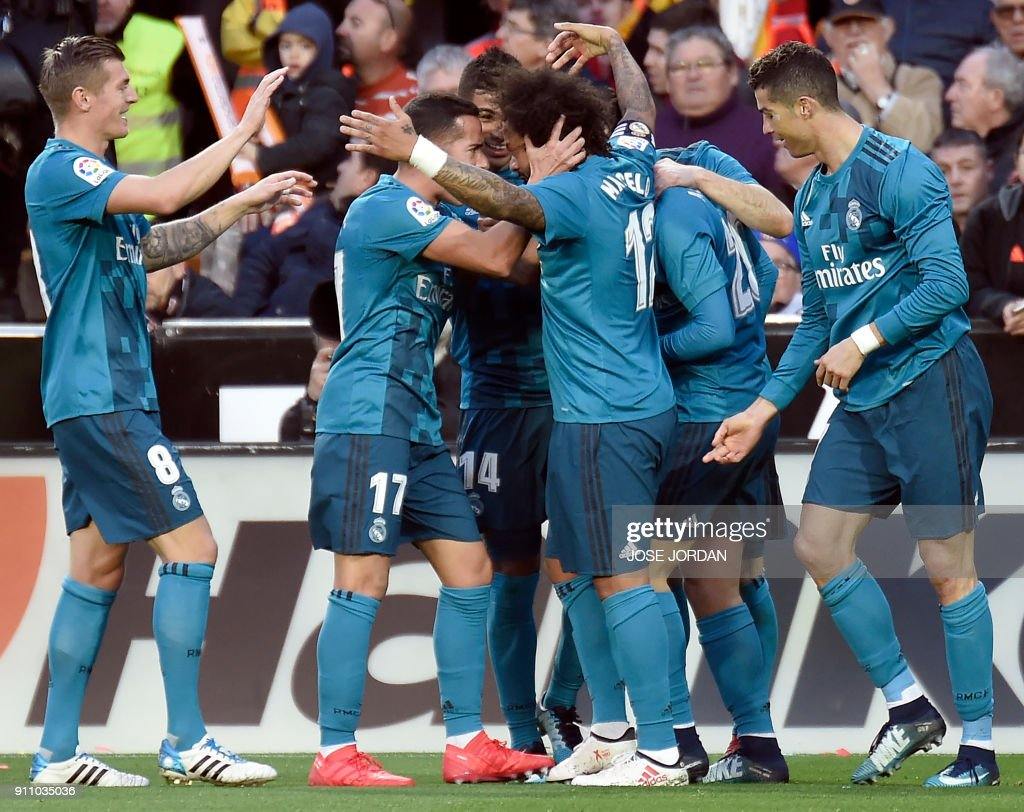 Real Madrid's Brazilian defender Marcelo (C) celebrates a goal with teammates during the Spanish league football match between Valencia CF and Real Madrid CF at the Mestalla stadium in Valencia on January 27, 2018. /