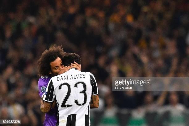 Real Madrid's Brazilian defender Marcelo embraces Juventus' Brazilian defender Dani Alves after a comingtogether during the UEFA Champions League...