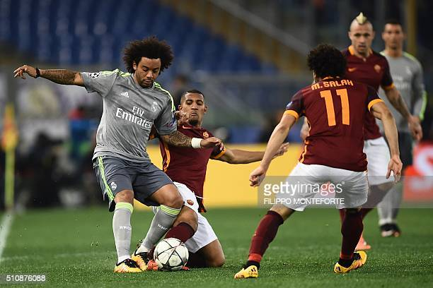 Real Madrid's Brazilian defender Marcelo fights for the ball with Roma's midfielder from Egypt Mohamed Salah and Roma's forward William Vainqueur...