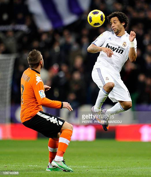 Real Madrid's Brazilian defender Marcelo heads the ball as he vies with Valencia's midfielder Joaquin Sanchez during the Spanish league football...