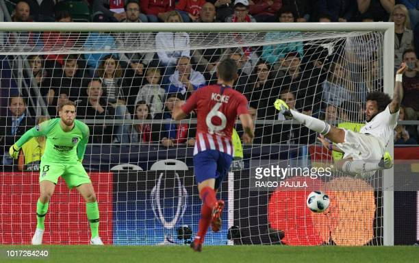 TOPSHOT Real Madrid's Brazilian defender Marcelo plays the ball as Atletico Madrid's Slovenian goalkeeper Jan Oblak and Atletico Madrid's Spanish...