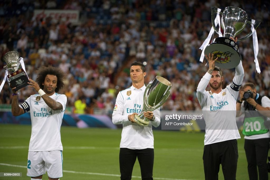 Real Madrid's Brazilian defender Marcelo, Real Madrid's Portuguese forward Cristiano Ronaldo and Real Madrid's defender Sergio Ramos hold respectively the Spanish Supercup, the Europe Super cup, and the Spanish League cup before the Spanish league football match Real Madrid CF vs Valencia CF at the Santiago Bernabeu stadium in Madrid on August 27, 2017. /