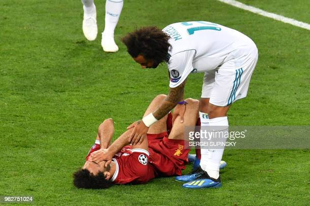 Real Madrid's Brazilian defender Marcelo stands next to Liverpool's Egyptian forward Mohamed Salah laying on the pitch after injury during the UEFA...
