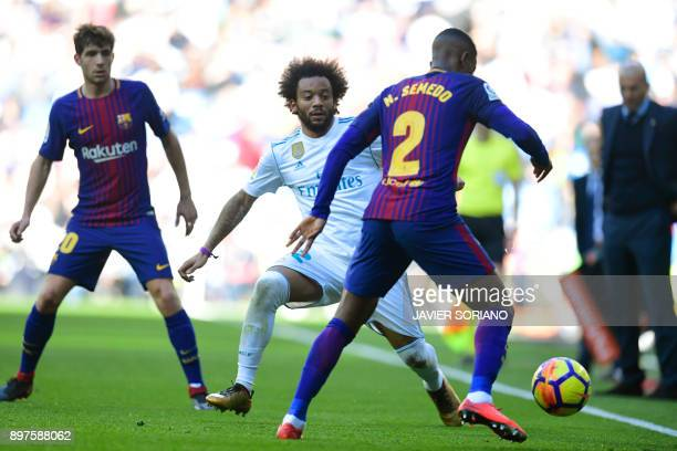 Real Madrid's Brazilian defender Marcelo vies with Barcelona's Portuguese defender Nelson Semedo during the Spanish League 'Clasico' football match...