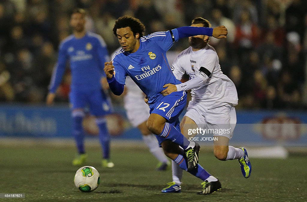 Real Madrid's Brazilian defender Marcelo (L) vies with Olimpic's midfielder Dennis during the Spanish Copa del Rey (King's Cup) finals stage match Olimpic de Xativa vs Real Madrid CF at the La Murta stadium in Xativa on December 7, 2013.