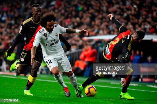 Real Madrid's Brazilian defender Marcelo vies with Rayo Vallecano's Spanish defender Tito and Rayo Vallecano's Peruvian defender Luis Advincula...