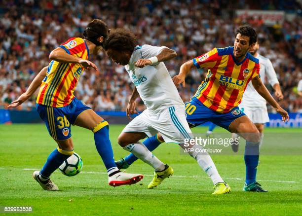 Real Madrid's Brazilian defender Marcelo vies with Valencia's midfielder Nacho Vidal and Valencia's midfielder Daniel Parejo during the Spanish...