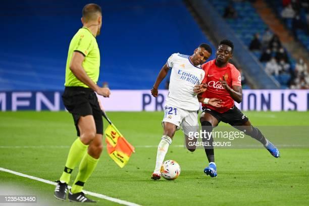 Real Madrid's Brazilian forward Rodrygo is challenged by Real Mallorca's Ghanaian midfielder Iddrisu Baba during the Spanish League footbal match...