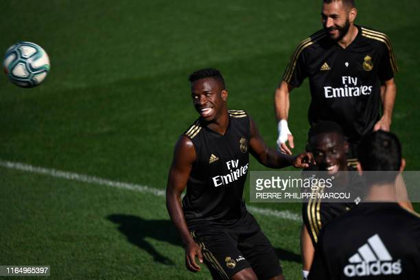 Real Madrid's Brazilian forward Vinicius Junior and Real Madrid's French forward Karim Benzema eye the ball during a training session at the Ciudad...