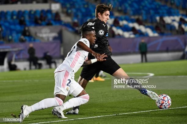 Real Madrid's Brazilian forward Vinicius Junior challenges Moenchengladbach's German midfielder Christoph Kramer during the UEFA Champions League...