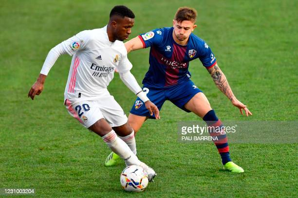 Real Madrid's Brazilian forward Vinicius Junior challenges Huesca's Spanish defender Pablo Maffeo during the Spanish league football match between SD...
