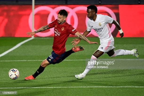 Real Madrid's Brazilian forward Vinicius Junior challenges Osasuna's Spanish midfielder Ruben Garcia during the Spanish League football match between...